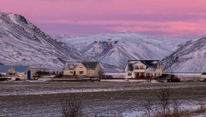 Modern homes on farm land with mountains behind the homes - improve your home energy efficiency